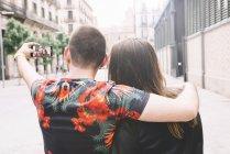 Vista trasera de la pareja tomando una selfie con smartphone - foto de stock