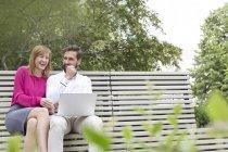 Laughing man woman sitting on bench using laptop — Stock Photo