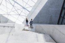 Dos empresarios en patines en la arquitectura moderna - foto de stock