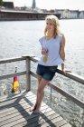 Souriante jeune femme avec une bouteille de bière sur un bateau maison — Photo de stock