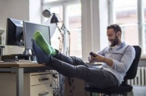 Giovane in ufficio con i piedi sulla scrivania indossando calzini diversi — Foto stock
