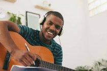 Человек с гитарой слушает музыку с наушниками — стоковое фото