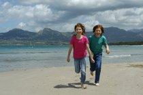 France, Corsica , Calvi, two children running on sandy beach — Stock Photo