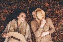 Due amiche sorridenti sdraiate fianco a fianco su foglie autunnali in un parco — Foto stock