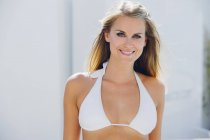 Portrait of smiling blond woman wearing bikini top — Stock Photo