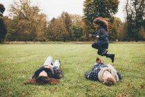 Молодые родители, лежа на лугу во время маленькая девочка, перепрыгивая через них в парке — стоковое фото