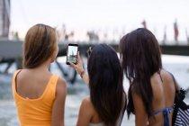 Mexique, Puerto Vallarta, trois jeunes femmes prenant une photo smartphone de jetée Los Muertos — Photo de stock