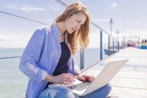 Mujer usando portátil en embarcadero cerca del mar - foto de stock