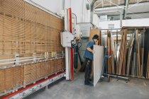 Prendendo il bordo di legno dall'archivio del carpentiere — Foto stock