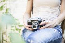 Крупным планом женщина держит камеру сидящим на скамейке — стоковое фото