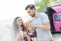 Jeune couple avec des sandwichs à l'extérieur — Photo de stock