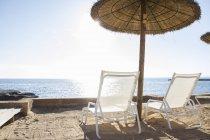 Spagna, Maiorca, Ombrelli di paglia e amache di fronte al mare — Foto stock