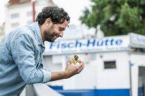 Улыбающийся мужчина с рыбным сэндвичем — стоковое фото