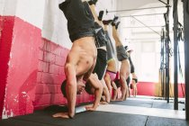 CrossFit athletes doing handstand push-ups at a wall — Stock Photo