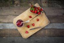 Vaso de mermelada de fresa casera y caja de fresas frescas en tablero de madera - foto de stock