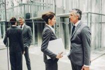 Zwei Geschäftspartner sprechen in einem Bürogebäude Korridor — Stockfoto