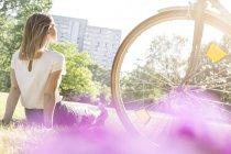 Femme assise sur le pré à côté de la bicyclette — Photo de stock