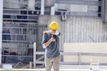 Man with cell phone wearing hard hat on construction site — Stock Photo