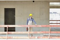 Man with hard hat on construction site standing at railing — Stock Photo
