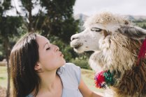 Peru, Cusco, young woman standing face to face to alpaca — Stock Photo