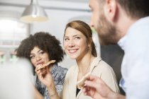 Três colegas no escritório, comendo pizza — Fotografia de Stock