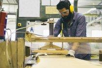 Handwerker mit Gehörschutz, Handschuhe und Schutzbrille mit einem industriellen Kreissäge in einer Fabrik — Stockfoto