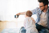 Padre sentado en la manta con su hija pequeña y tomando selfie - foto de stock