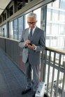 Leitenden Geschäftsmann stehend auf Büro Korridor auf Handy — Stockfoto