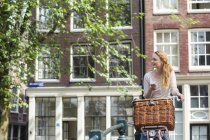 Netherlands, Amsterdam, woman with bicycle and cell phone in the city — Stock Photo