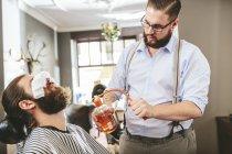 Pulverización para después del afeitado de la barba de un cliente del peluquero - foto de stock