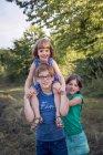 Retrato de menino com duas irmãzinhas permanente ao ar livre — Fotografia de Stock