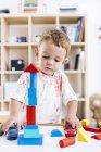 Маленький мальчик, строительство башни с голубой и красный кирпич строительный — стоковое фото