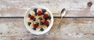 Bowl of muesli with banana slices, raspberries and blueberries — Stock Photo