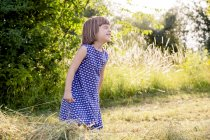 Petite fille debout dans le champ de foin avec les yeux fermés — Photo de stock