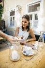 Jovem sentada no restaurante escrevendo cartões postais e bolo — Fotografia de Stock