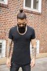 Retrato de jovem com barba cheia, pão e braços tatuados — Fotografia de Stock