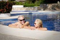 Happy senior couple in swimming pool — Stock Photo