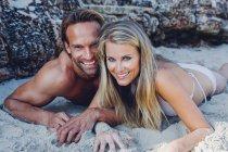 Paar liegt am Sandstrand — Stockfoto