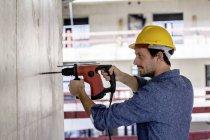 Homem com chapéu duro no local de construção utilizando broca — Fotografia de Stock