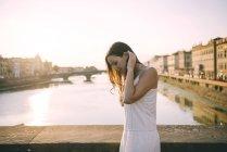 Itália, Florença, mulher feliz vestindo vestido de verão branco em pé em uma ponte ao pôr do sol — Fotografia de Stock