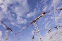 Deutschland, Berlin, Krane auf Baustelle gegen Himmel — Stockfoto