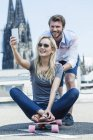 Germany, Cologne, portrait of smiling young couple taking a selfie with smartphone — Stock Photo
