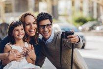Homme tenant à l'extérieur un selfie de sa famille avec appareil photo numérique — Photo de stock