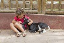 Маленькая девочка гладит козу — стоковое фото
