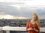 Germania, Berlino, giovane donna che guarda il suo smartphone — Foto stock