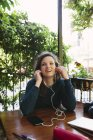 Mujer joven en el balcón escuchando música con teléfono inteligente - foto de stock