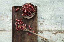 Bowl and spoon with pomegranate seed on wooden tray — Stock Photo