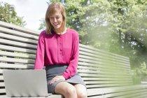 Donna che si siede sulla panchina e usando il portatile — Foto stock