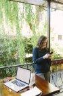 Молода жінка, сидячи на балконі, використовуючи ноутбук і смарт-телефон — стокове фото