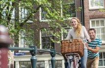 Pays-Bas, Amsterdam, couple heureux avec vélo dans la ville — Photo de stock